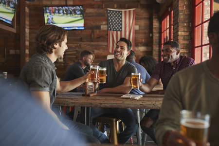 Group Of Male Friends Meeting And Drinking Beer In Sports Bar Together Stock Photo
