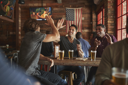 Group Of Male Friends Celebrating Whilst Watching Game On Screen In Sports Bar