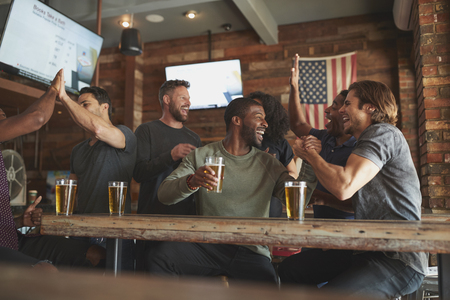 Group Of Friends Watching Game On Screen In Sports Bar Stock Photo