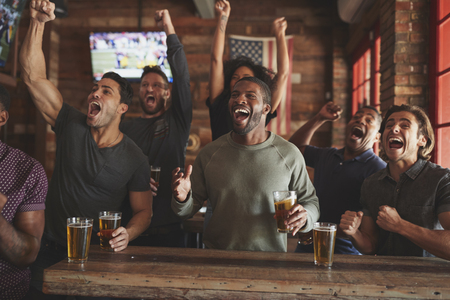 Group Of Male Friends Celebrating Whilst Watching Game On Screen In Sports Bar 写真素材 - 115757183