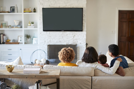 Back view of young family sitting on the sofa and watching TV together in their living room Imagens