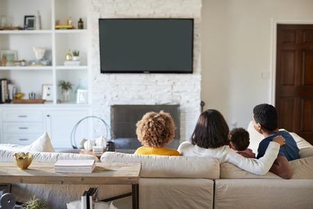 Rückansicht einer jungen Familie, die auf dem Sofa sitzt und zusammen in ihrem Wohnzimmer fernsieht