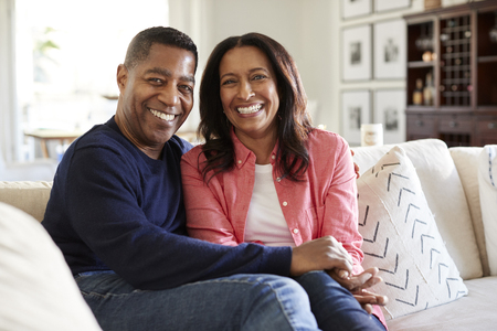 Middle aged mixed race couple sitting on the sofa in their living room looking to camera, front view, close up