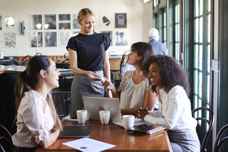Businesswomen Paying Bill At Meeting Around Table In Coffee Shop Stock Photo