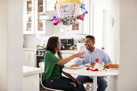 Middle aged mixed race couple making a toast over a romantic birthday meal in their kitchen, close up Stockfoto
