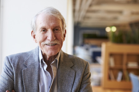 Portrait Of Smiling Senior Businessman In Modern Office Standing By Window Stock fotó