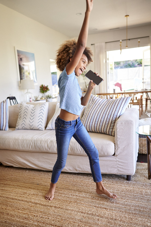 Pre-teen black girl dancing and singing in the living room at home using her phone as a microphone, side view, full length, vertical