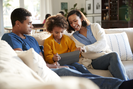 Young parents and their pre-teen daughter sitting on a sofa in the living room using a tablet computer together, selective focus