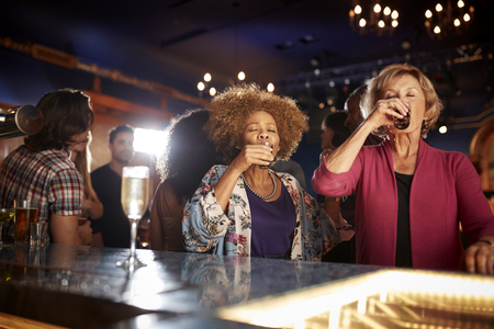 Female Senior Friends Drinking Shots In Bar Together