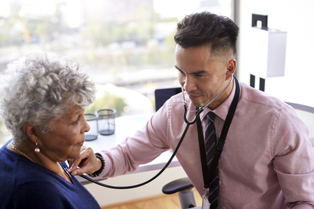 Male Doctor In Office Listening To Senior Female Patients Chest Using Stethoscope Stock Photo