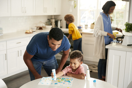 Dad watching his toddler son painting a picture sitting at a table in the kitchen, while mother and girl prepare food in the background Stock Photo