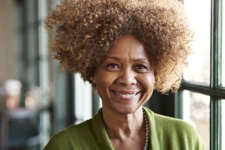 Porträt der lächelnden älteren Frau, die im Restaurant sitzt?