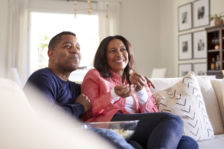 Close up of middle aged couple sitting on the sofa in their living room watching TV, laughing and eating popcorn, close up Stockfoto