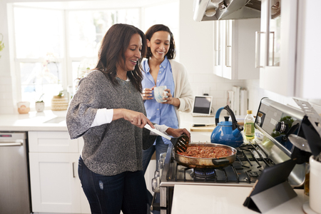 Middle aged woman standing in the kitchen cooking at hob following recipe on a tablet computer, her adult daughter standing beside her talking, side view