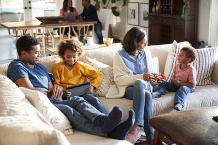 Three generation family family spending time in their open plan living room, grandparents in the background, elevated view