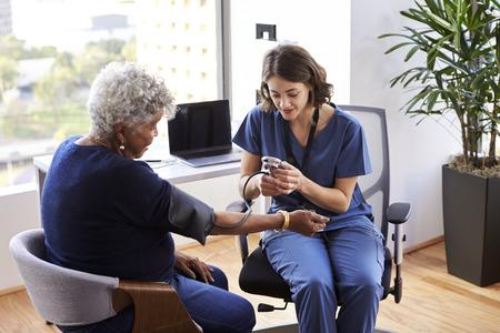 Enfermera vistiendo matorrales en la oficina comprobando la presión arterial de las pacientes mayores