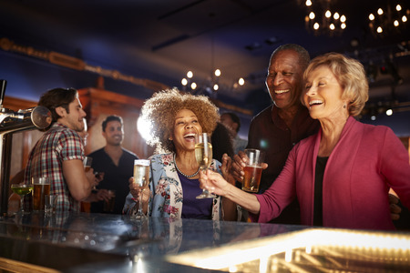 Group Of Senior Friends Drinking In Bar Together Stock Photo