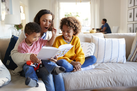 Close up of young mother sitting on a sofa in the living room reading a book to her two children, father sitting at a table in the background, focus on foreground