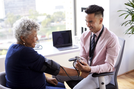 Male Doctor In Office Checking Senior Female Patients Blood Pressure Stock Photo