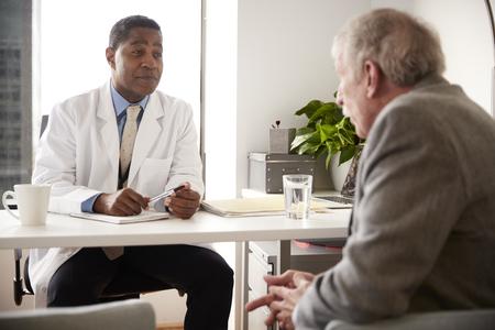 Älterer Mann, der sich mit einem männlichen Arzt im Krankenhausbüro beraten lässt