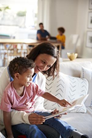 Close up van jonge moeder zittend op een bank in de woonkamer een boek lezen met haar peuter zoon, zittend op haar knie, vader en dochter zittend aan een tafel op de achtergrond, verticaal