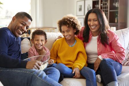 Jeugdige grootouders zitten met hun kleinkinderen op de bank in de woonkamer popcorn te eten en te lachen, vooraanzicht, close-up