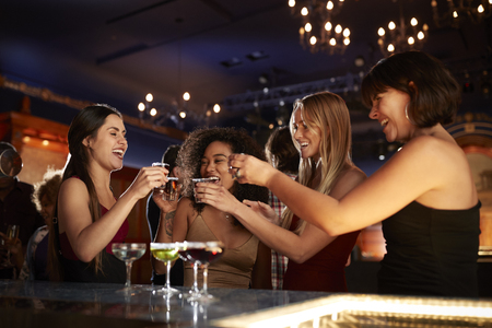 Group Of Female Friends Drinking Shots In Cocktail Bar Together Stock Photo