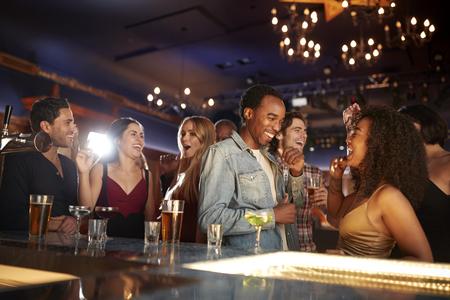 Gruppe von Paaren mit Freunden, die zusammen in der Bar trinken