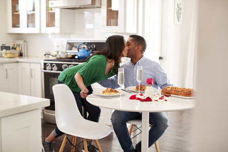 Middle aged mixed race woman woman kissing her partner after serving him a romantic meal in their kitchen, selective focus