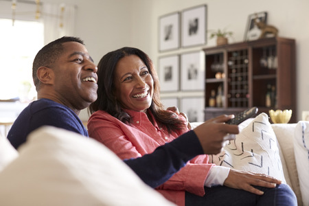 Close up of middle aged couple sitting on the sofa in their living room using remote and watching TV, laughing, close up Stockfoto