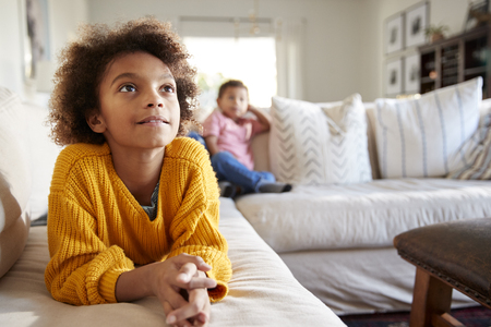 Close up of pre-teen girl lying on sofa watching TV in the living room, her younger brother sitting in the background, focus on foreground Stock Photo