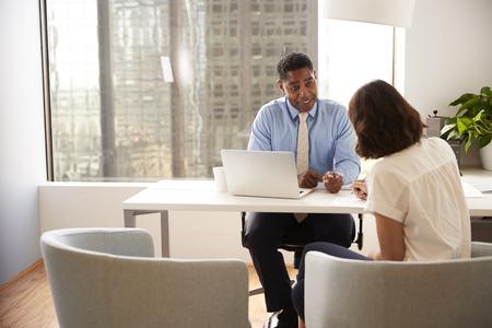 Cliente femenino firmando documento en reunión con asesor financiero masculino en Office