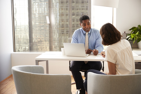 Documento di firma del cliente femminile nell'incontro con il consulente finanziario maschile in ufficio