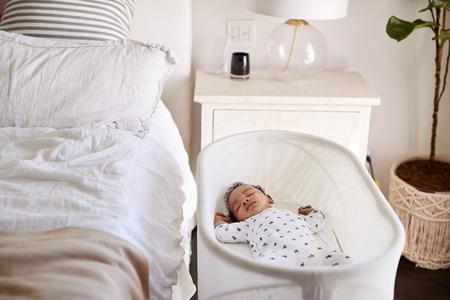 Drei Monate altes Baby schläft in seinem Bettchen neben dem Bett im Schlafzimmer seiner Mutter Standard-Bild