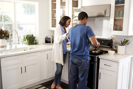 Back view of young couple standing in the kitchen preparing food together