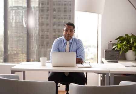 Portrait Of Male Financial Advisor In Modern Office Sitting At Desk Working On Laptop