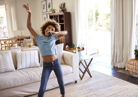 Pre-teen girl dancing and singing along to music in the living room at home using her phone as a microphone, three quarter length Stockfoto
