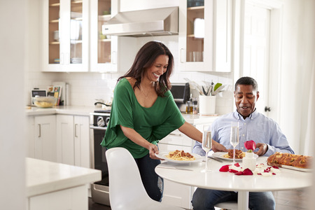 Middle aged mixed race woman woman serving her partner a romantic meal in their kitchen, selective focus
