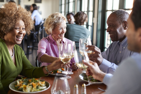 Group Of Smiling Senior Friends Meeting For Meal In Restaurant