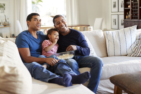 Three generation family male family group sitting on a sofa in the living room eating popcorn and watching TV, selective focus Imagens