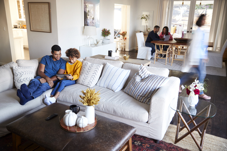 Three generation family family spending time in their open plan living room and kitchen diner, father and daughter in the foreground, elevated view, motion blur Stockfoto