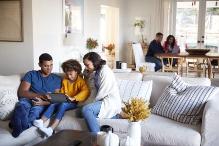 Jonge ouders zitten op de bank met hun dochter die tabletcomputer gebruikt in de open woonkamer, grootouders zitten aan een tafel op de achtergrond