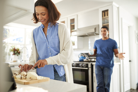 Young mixed race woman standing in the kitchen preparing food, her partner standing behind talking, focus on foreground