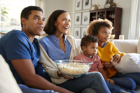 Young family sitting together on the sofa in their living room watching TV and eating popcorn, side view
