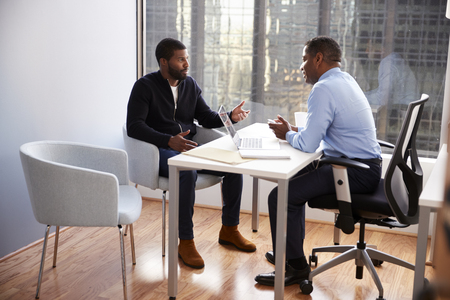 Man Meeting With Male Financial Advisor Relationship Counsellor In Office