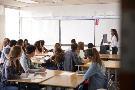 Female High School Teacher Standing By Interactive Whiteboard Teaching Lesson 版權商用圖片