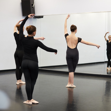 Female Students At Performing Arts School Rehearsing Ballet In Dance Studio Reflected In Mirror Stock Photo