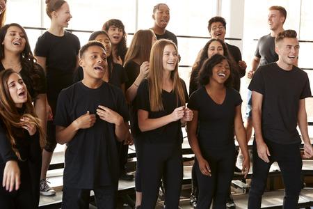 Estudiantes masculinos y femeninos cantando en coro en la escuela de artes escénicas Foto de archivo