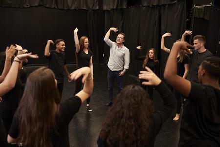 Leraar met mannelijke en vrouwelijke dramastudenten op de school voor uitvoerende kunsten in de studio-improvisatieklas
