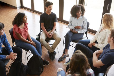 Female Tutor Leading Discussion Group Amongst High School Pupils Stock Photo